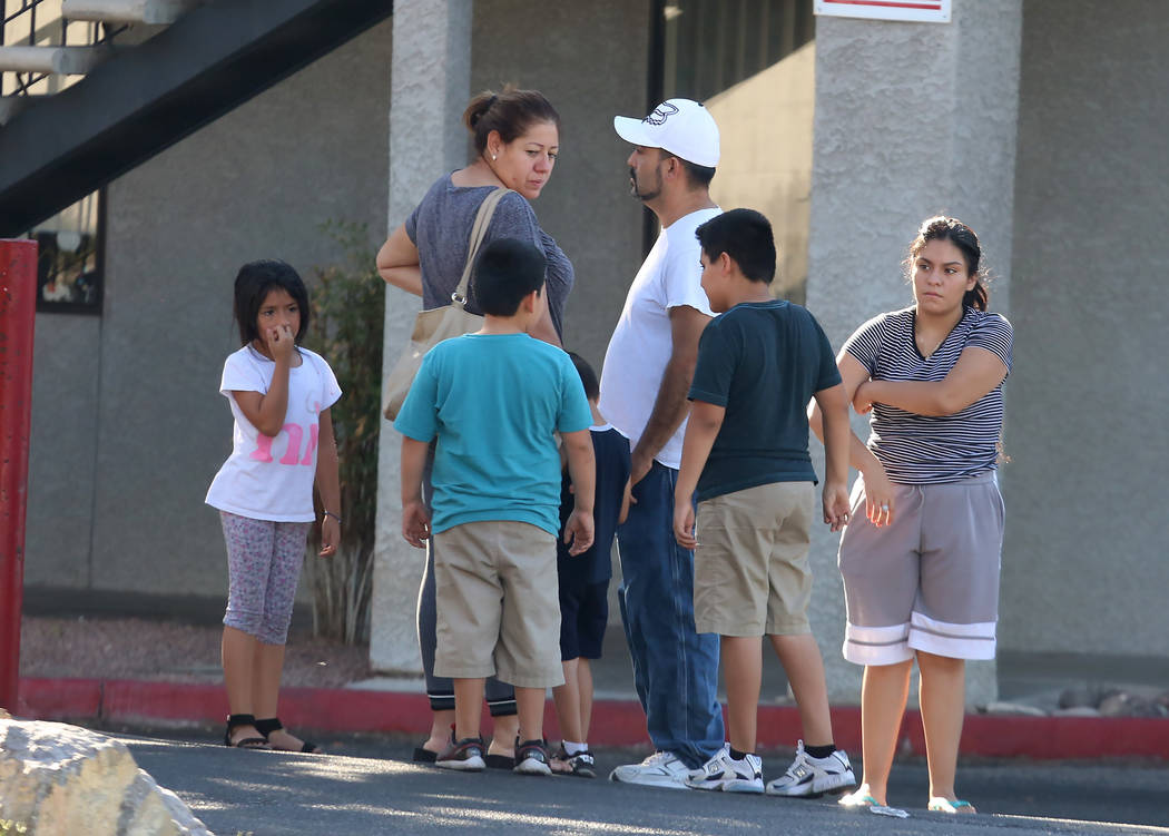 Residents gather outside an apartment complex where Metro police are working at the scene of a stabbing and barricade situation on Boulder Highway near Nellis Boulevard in Las Vegas on Wednesday,  ...
