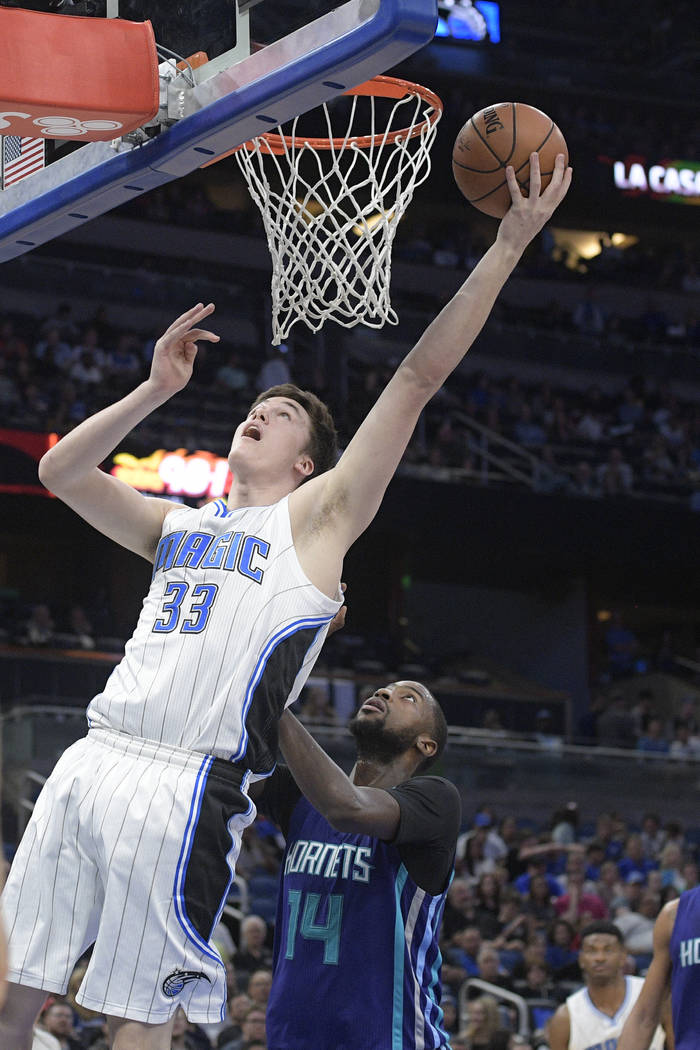 Orlando Magic center Stephen Zimmerman (33) goes up for a shot in front of Charlotte Hornets forward Michael Kidd-Gilchrist (14) during the second half of an NBA basketball game in Orlando, Fla.,  ...