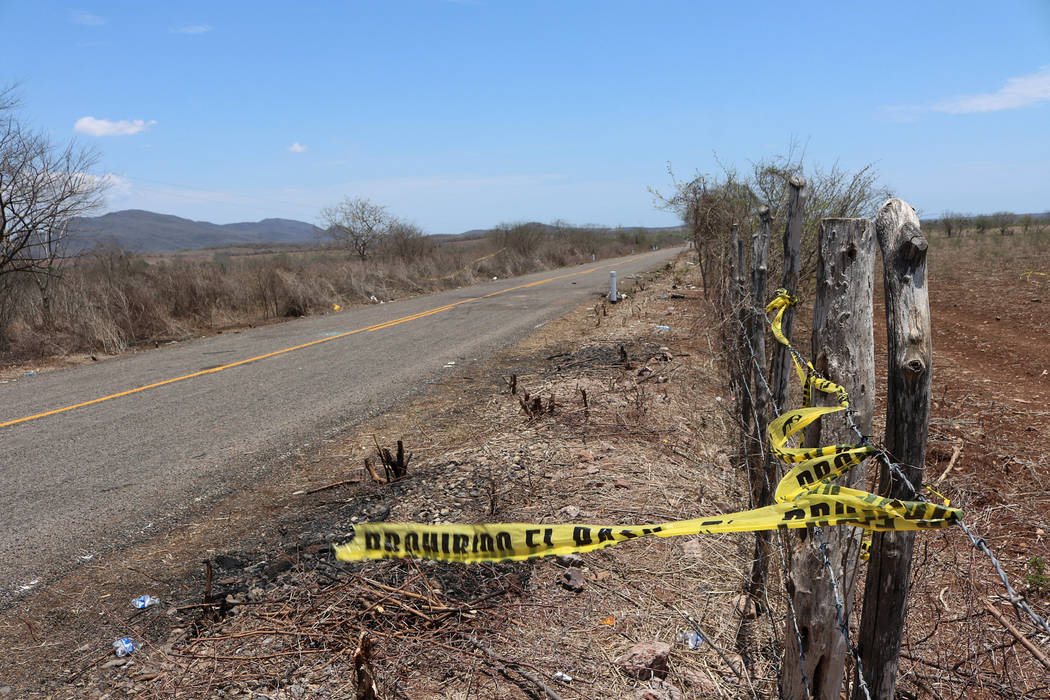 A police cordon tied to barbed-wire fence is seen in an area of a crime scene after people were killed during shootouts between police and gunmen on the road to the town of Aguaje de Costilla, nea ...