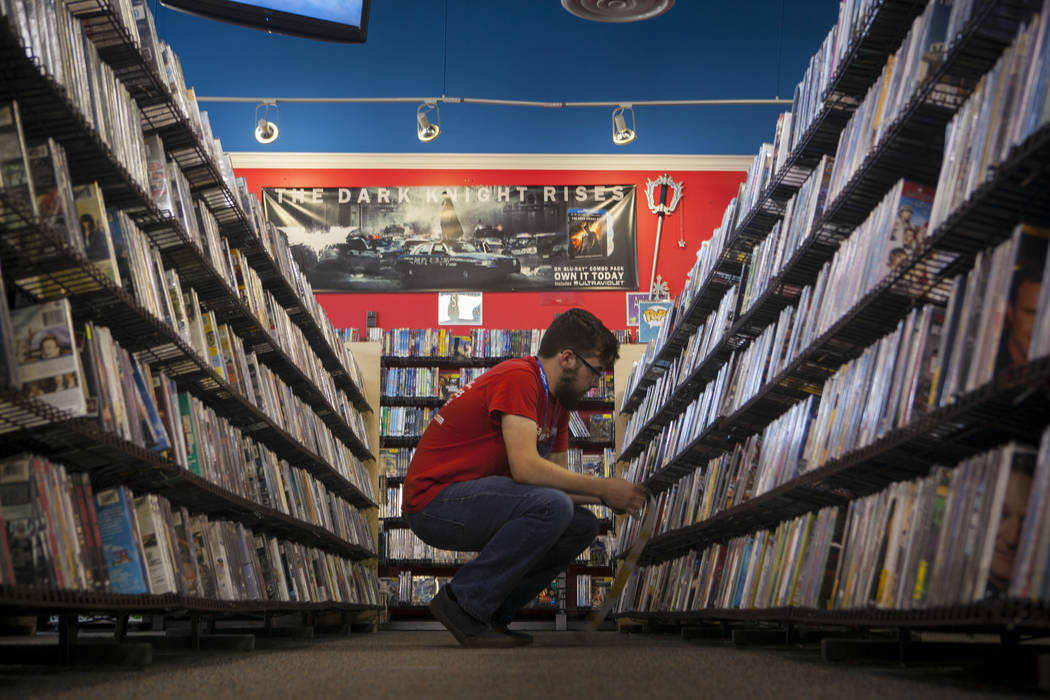 An employee works a movie section at a Vintage Stock store in Kansas City, Missouri. Vintage Stock is one of two companies owned by Las Vegas Valley-based holding company Live Ventures. (Vintage S ...