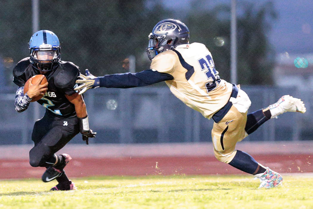 Cheyenne junior Clarence Rose (32) reaches out for Canyon Springs junior Diamante Burton (2) during a football matchup at Canyon Springs High School, 350 East Alexander Rd, North Las Vegas, Friday ...
