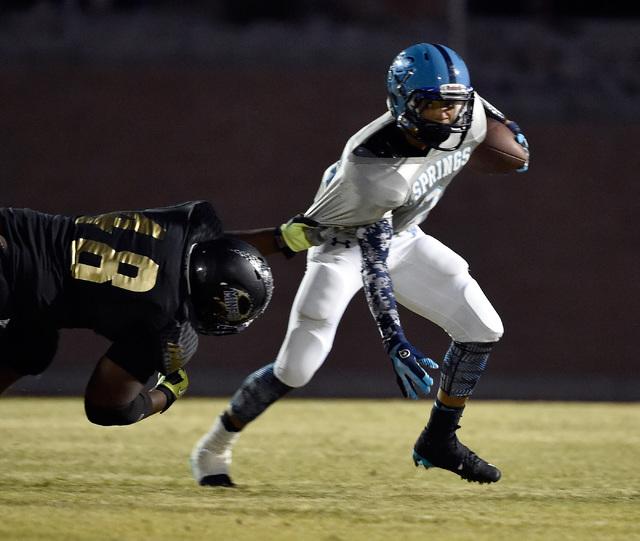 Canyon Springs quarterback Diamante Burton runs with the ball against Sunrise Mountain's Ja'twion Farmer during a high school football game at Sunrise Mountain High School Friday, Sept. 16, 2016,  ...