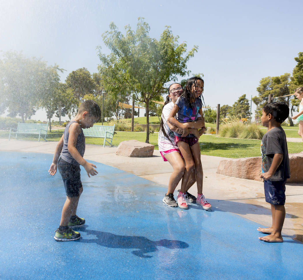 Kids play on a splash pad at Craig Ranch Regional Park in Las Vegas, Thursday, July 6, 2017. (Elizabeth Brumley/Las Vegas Review-Journal)