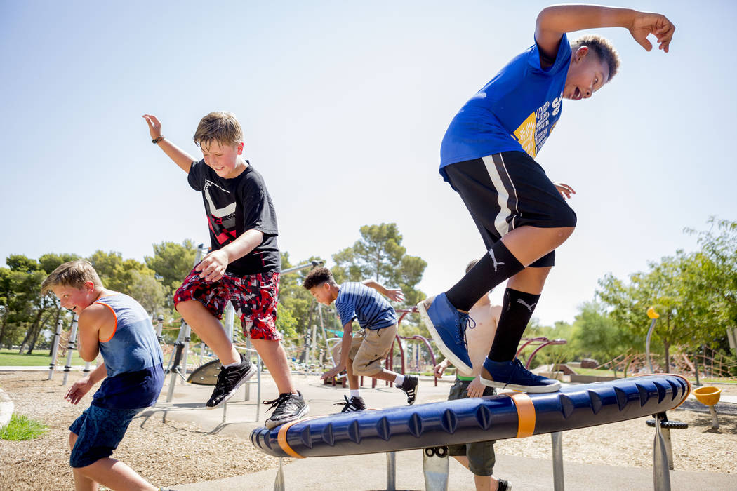 Friends see how long they can stay on a moving wheel at Craig Ranch Regional Park in Las Vegas, Thursday, July 6, 2017. (Elizabeth Brumley/Las Vegas Review-Journal)