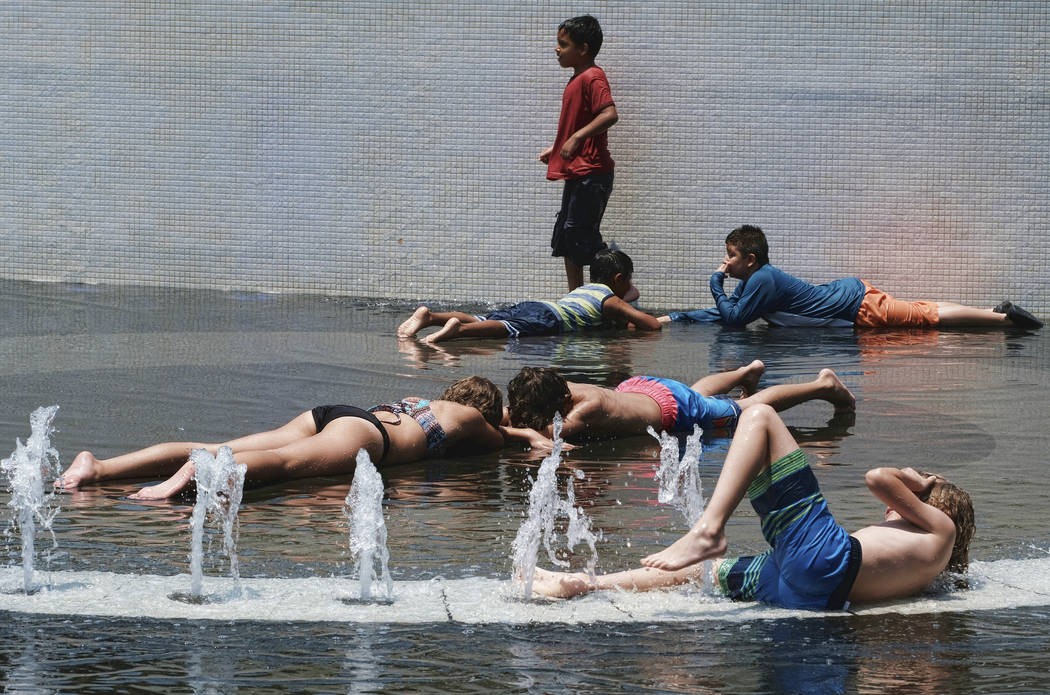 Children try to cool down and take advantage of the Grand Park fountain in downtown Los Angeles on Wednesday, July 5, 2017. Forecasters say a new heat wave is setting in across the interior of Sou ...