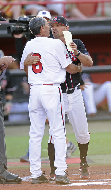 UNLV Rebels head coach Tim Chambers and San Diego State Aztecs assistant head coach Mark Martinez embrace before the start of the 2014 Mountain West Conference Baseball Championship game at Earl E ...