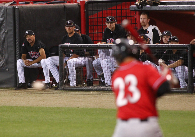 UNLV players and staff, including head coach Tim Chambers on far left, watch as San Diego State's Brad Haynal receives a pitch from UNLV during a game in the Mountain West baseball tournament at E ...