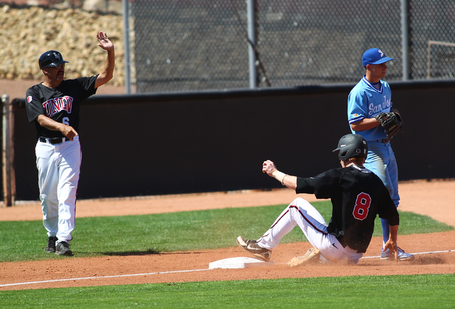 UNLV head coach Tim Chambers (6) motions to players as Erik VanMeetren (8)slides into third base against San Jose State's Mike Simonini (20) during a game at Earl E. Wilson Stadium in Las Vegas on ...