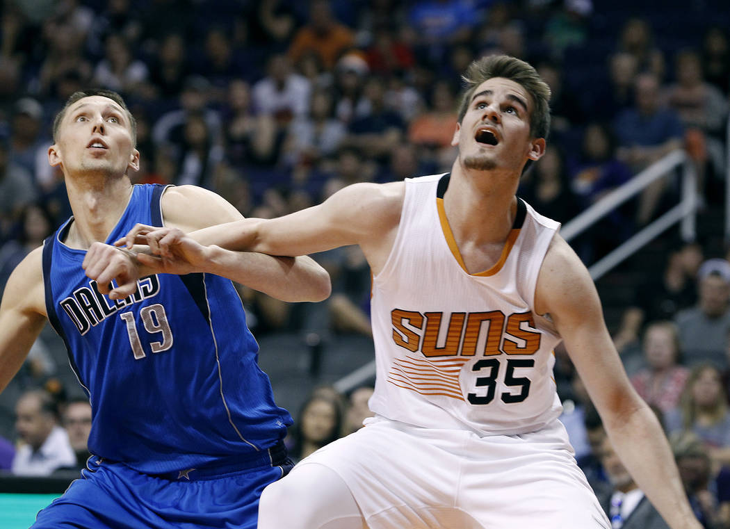 Phoenix Suns forward Dragan Bender (35) and Dallas Mavericks' Jarrod Uthoff (19) battle for position under the basket during the second half of an NBA basketball game, Sunday, April 9, 2017, in Ph ...