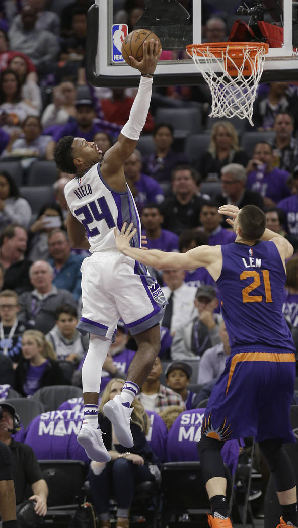 Sacramento Kings guard Buddy Hield, left, drives to the basket against Phoenix Suns center Alex Len during the second half of an NBA basketball game Tuesday, April 11, 2017, in Sacramento, Calif.  ...