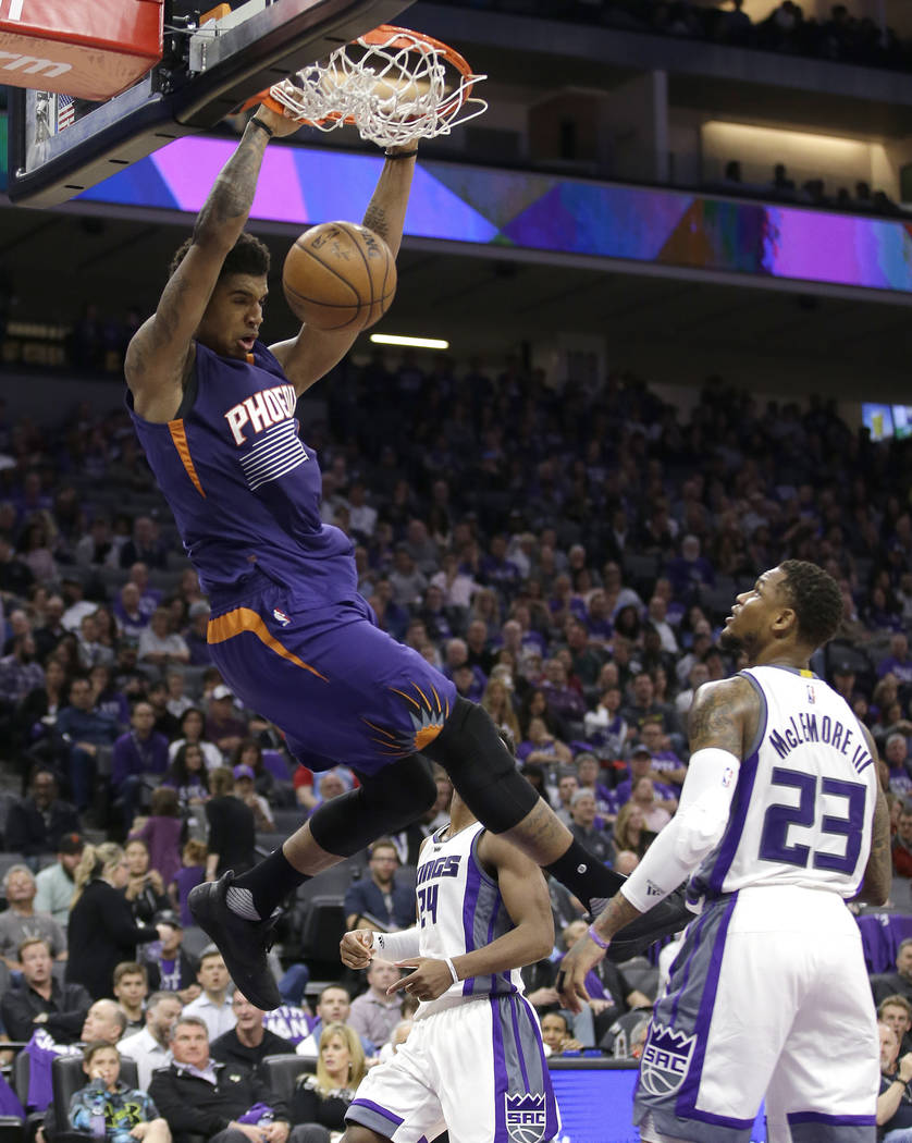 Phoenix Suns forward Marquese Chriss, left, hangs on the rim after stuffing over Sacramento Kings guard Ben McLemore during the second half of an NBA basketball game Tuesday, April 11, 2017, in Sa ...