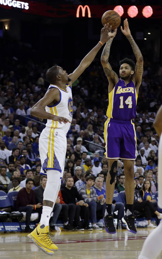 Los Angeles Lakers' Brandon Ingram (14) shoots over Golden State Warriors' Kevin Durant during the first half of an NBA basketball game Wednesday, April 12, 2017, in Oakland, Calif. (AP Photo/Marc ...