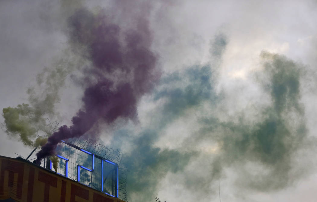 A demonstrator lights smoke markers on top of the Rote Flora squat during a protest against the G-20 summit in Hamburg, Germany, Wednesday, July 5, 2017. (Matthias Schrader/AP)