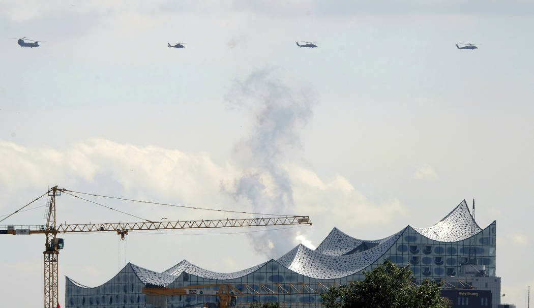 Helicopters - one of the them carrying U.S. President Donald Trump - fly over the Elbphilharmonie concert hall in Hamburg, northern Germany, Thursday, July 6, 2017 the day before the start of the  ...