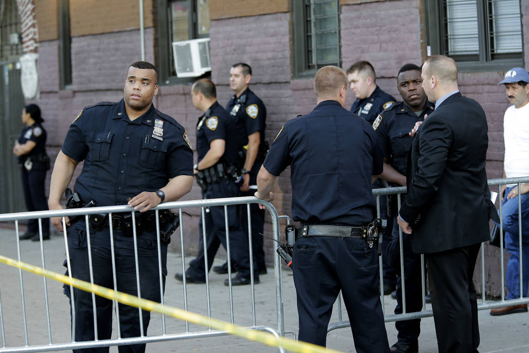 Emergency personnel stand near the scene where a police officer was shot in the Bronx section of New York, Wednesday, July 5, 2017. Police said Officer Miosotis Familia died at a hospital early We ...