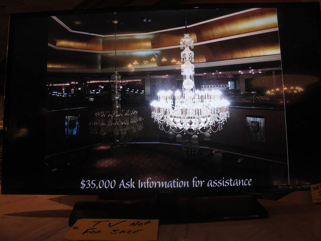 A video monitor displays an image of a crystal chandelier at the former Trump Taj Mahal casino in Atlantic City, N.J., on Thursday, July 6, 2017, during a sale of the casino hotel's contents. Incl ...