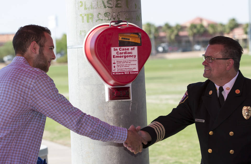 Adam Afromsky, left, and David Slattery, deputy chief of medical services for Las Vegas Fire and Rescue, shake hands after unveiling an automated external defibrillator (AED) at the Bettye Wilson  ...