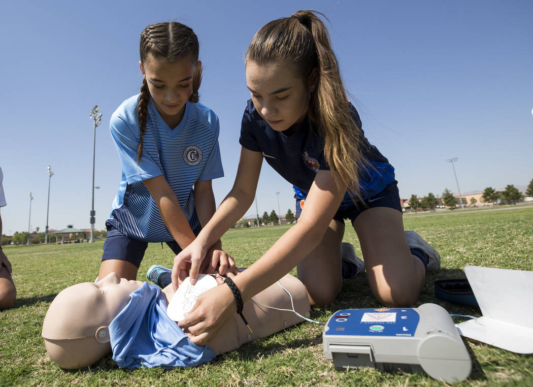 Youth soccer players Darien Cox, 9, left, and her sister Madison Cox, 14, demonstrate how to use an automated external defibrillator (AED) during an AED unveiling at the Bettye Wilson Soccer Compl ...