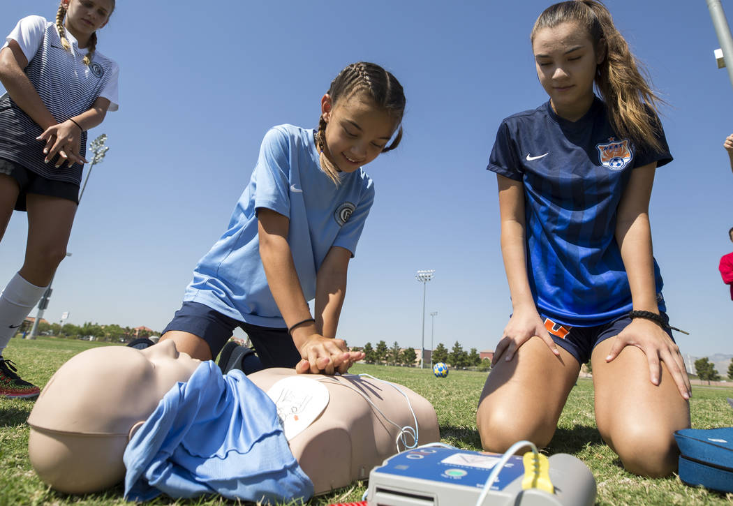 Youth soccer players Darien Cox, 9, center, and her sister Madison Cox, 14, right, demonstrate how to use an automated external defibrillator (AED) during an AED unveiling at the Bettye Wilson Soc ...