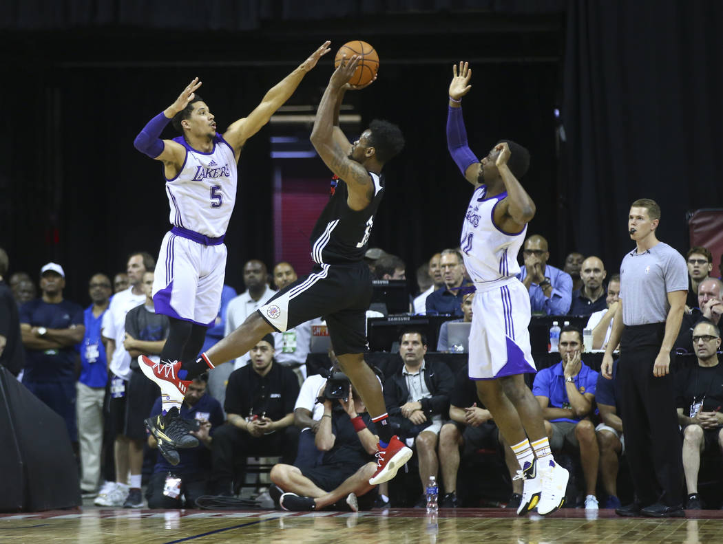 Los Angeles ClippersՠJames Bell, center, shoots over Los Angeles LakersՠJosh Hart (5) and during a basketball game at the NBA Summer League at the Thomas & Mack Center in Las Vegas ...