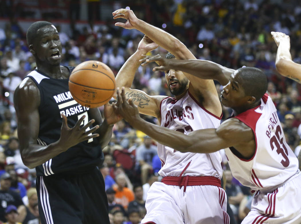 Milwaukee Bucks' Thon Maker, from left, Cleveland Cavaliers' Anthony Gill and Gerald Beverly fight for the ball during a basketball game at the NBA Summer League at the Thomas & Mack Center in ...