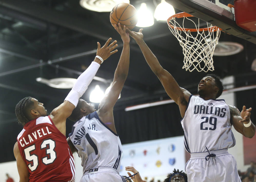 Dallas Mavericks' Dennis Smith Jr. (1) goes to the basket as Carrick Felix (29) assists while Miami Heat's Gian Clavell (53) defends during a basketball game at the NBA Summer League at the Thomas ...