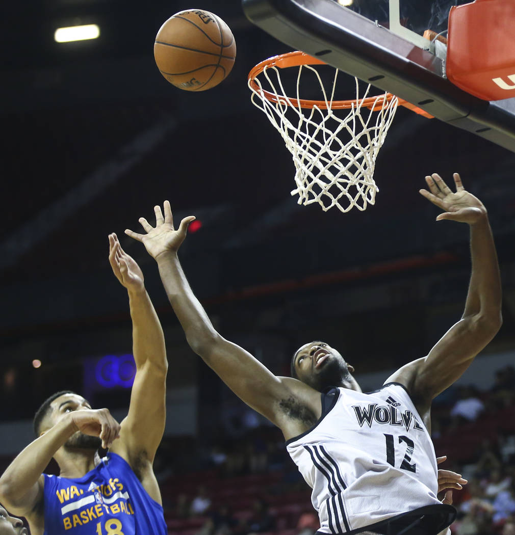 Minnesota Timberwolves' Amile Jefferson (12) reaches out for a rebound against Golden State Warriors' Noah Allen (18) during a basketball game at the NBA Summer League at the Thomas & Mack Cen ...
