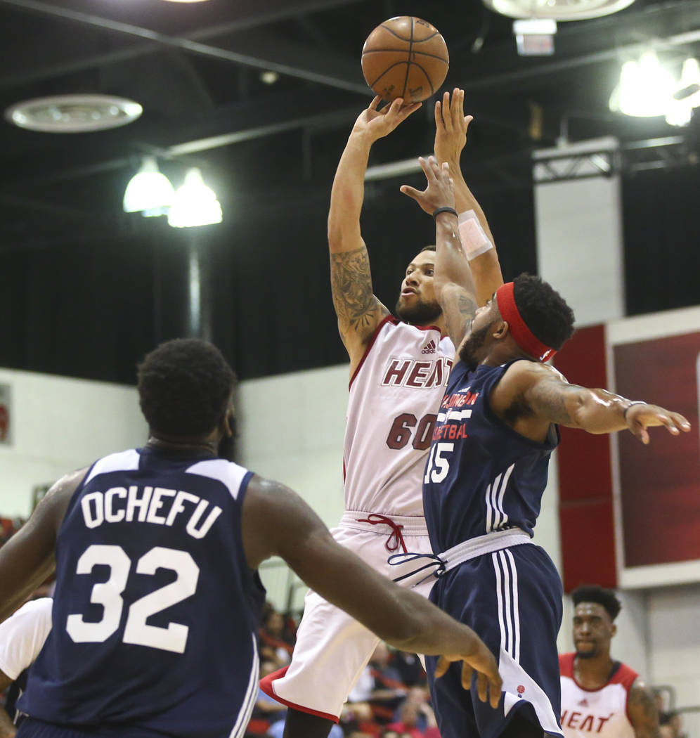 Miami Heat's Trey McKinney-Jones (60) goes up to shoot as Washington Wizards' Marcus Keene (15) defends during a basketball game at the NBA Summer League at the Cox Pavilion in Las Vegas on Wednes ...