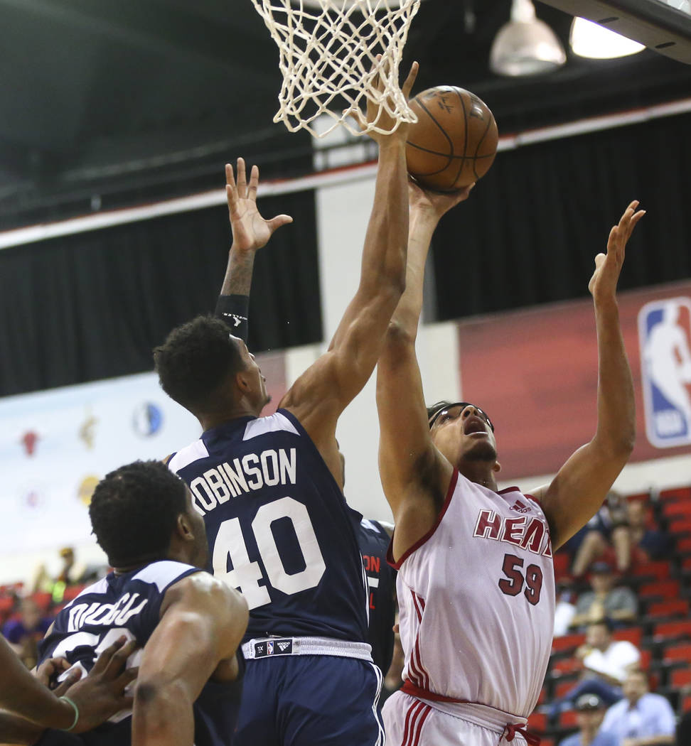 Miami Heat's Sebastian Saiz (59) goes to the basket against Washington Wizards' Devin Robinson (40) during a basketball game at the NBA Summer League at the Cox Pavilion in Las Vegas on Wednesday, ...