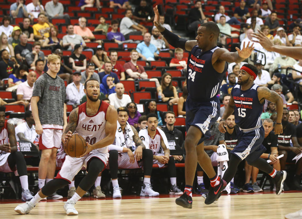 Miami Heat's Trey McKinney-Jones (60) looks to shoot as Washington Wizards' Michael Young (34) defends during a basketball game at the NBA Summer League at the Cox Pavilion in Las Vegas on Wednesd ...