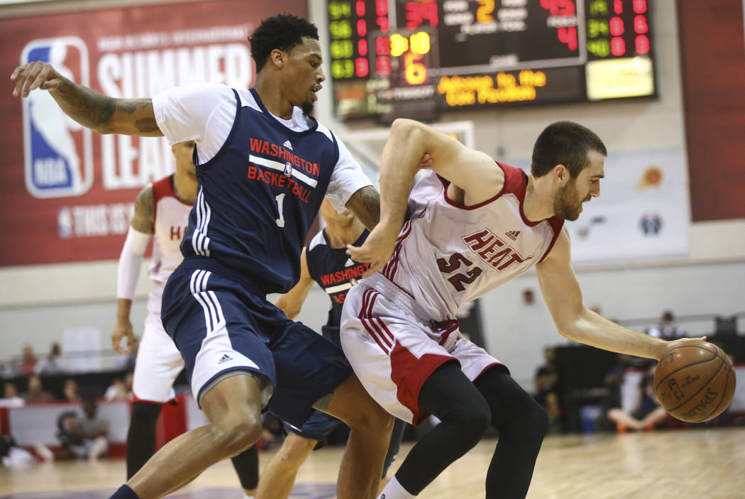 Miami Heat's Jake Odum (52) drives the ball past Washington Wizards' Chris McCullough (1) during a basketball game at the NBA Summer League at the Cox Pavilion in Las Vegas on Wednesday, July 12,  ...