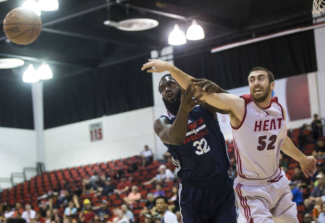 Washington Wizards' Daniel Ochefu (32) and Miami Heat's Jake Odum (52) reach for a rebound during a basketball game at the NBA Summer League at the Cox Pavilion in Las Vegas on Wednesday, July 12, ...