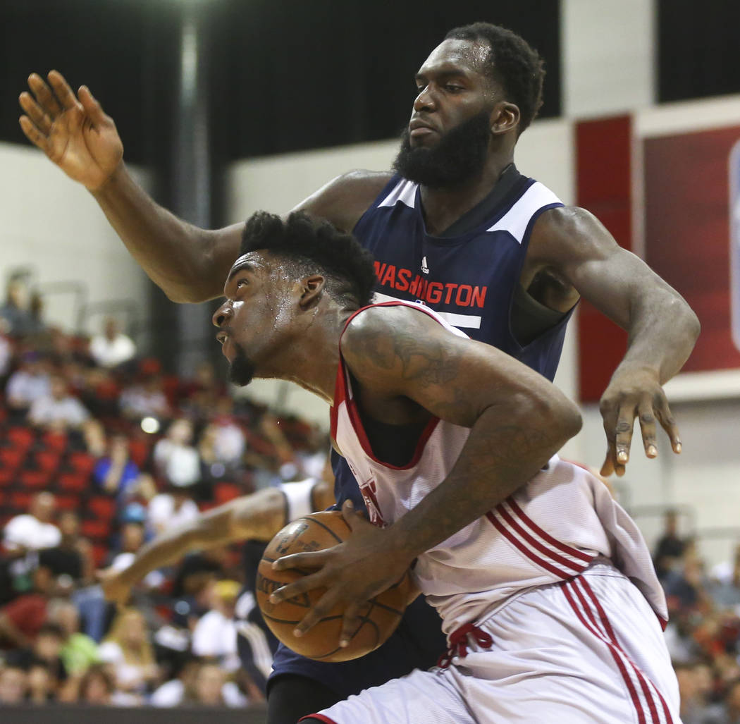 Miami Heat's Norvel Pelle (62) goes up to shoot against Washington Wizards' Daniel Ochefu during a basketball game at the NBA Summer League at the Cox Pavilion in Las Vegas on Wednesday, July 12,  ...