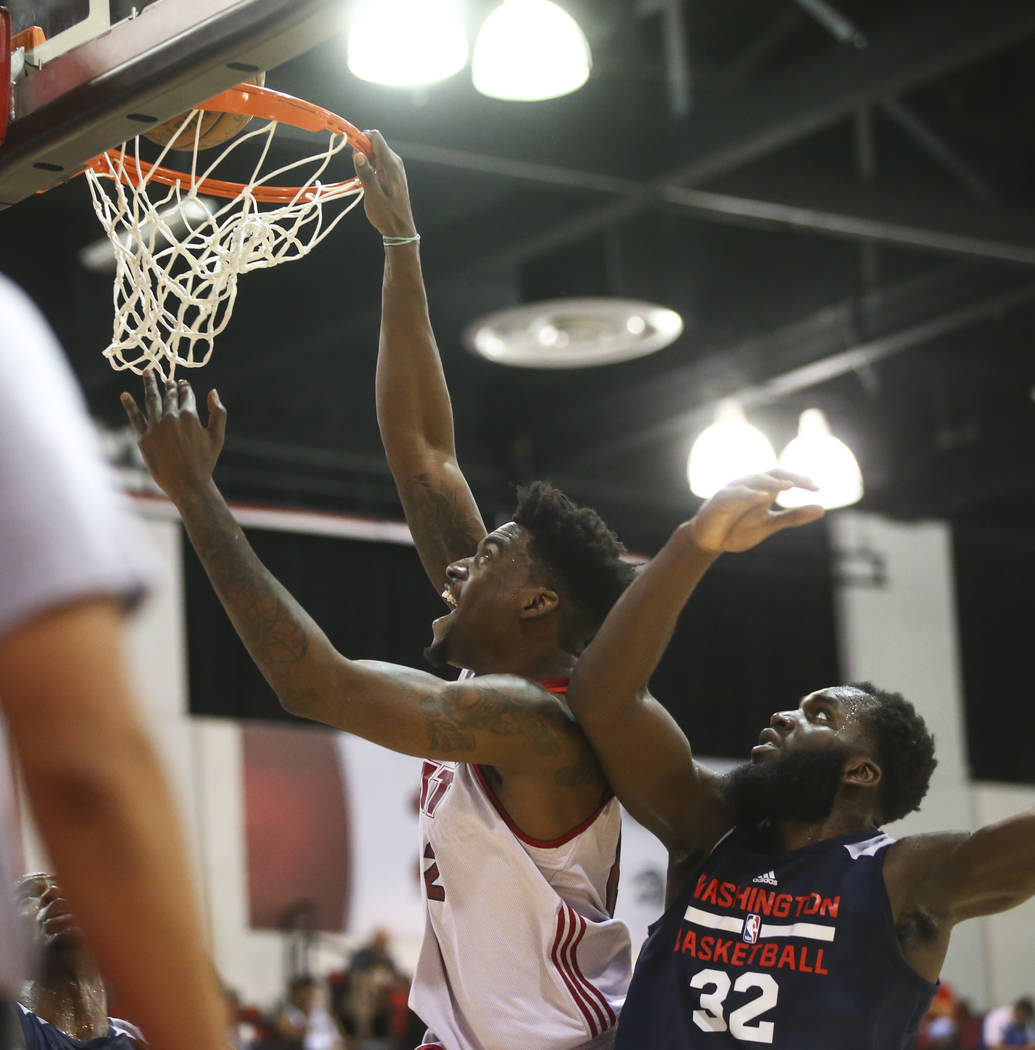 Miami Heat's Norvel Pelle (62) dunks against Washington Wizards' Daniel Ochefu (32) during a basketball game at the NBA Summer League at the Cox Pavilion in Las Vegas on Wednesday, July 12, 2017.  ...