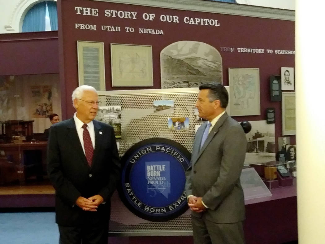 Gov. Brian Sandoval, right, and Bud Hicks, chairman of the Nevada 150 Foundation, visit before the foundation presents the state with a $700,000 check to renovate the Battle Born Hall exhibits at  ...
