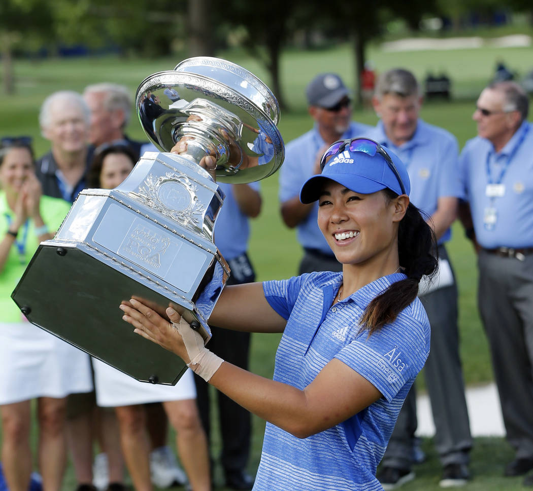 Danielle Kang raises the championship trophy after winning the Women's PGA Championship golf tournament at Olympia Fields Country Club, Sunday, July 2, 2017, in Olympia Fields, Ill. (AP Photo/Char ...