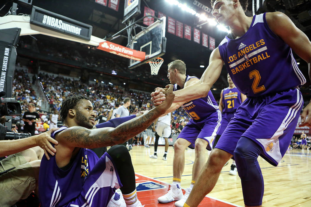 Los Angeles Lakers guard Lonzo Ball (2) helps up guard Vander Blue (1) after he falls to the ground during their 2017 NBA Summer League game against the Brooklyn Nets at Thomas & Mack in Las V ...