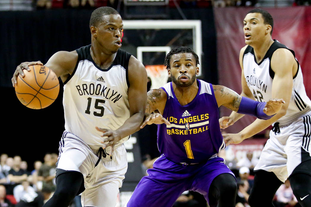 Los Angeles Lakers guard Vander Blue, center, attempts to guard Brooklyn Nets guard Isaiah Whitehead, left, during their 2017 NBA Summer League game at Thomas & Mack in Las Vegas on Saturday,  ...