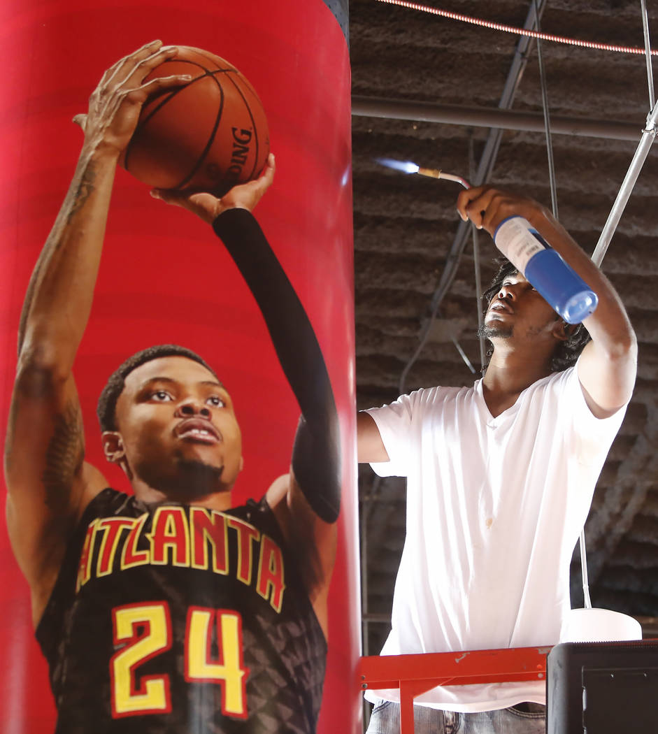 A worker installs a banner of Atlanta Hawks' Kent Bazemore for the 2017 NBA Summer League at the Thomas & Mack Center on Thursday, July 6, 2017. Bizuayehu Tesfaye/Las Vegas Review-Journal @biz ...