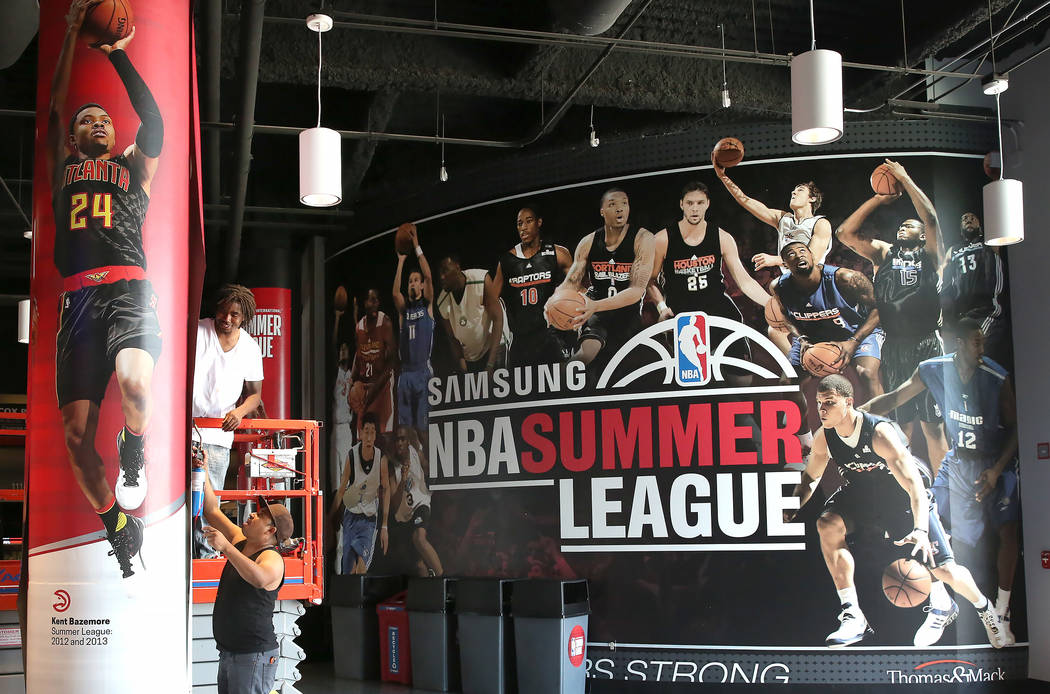 Workers install banners for the 2017 NBA Summer League at the Thomas & Mack Center on Thursday, July 6, 2017. Bizuayehu Tesfaye/Las Vegas Review-Journal @bizutesfaye