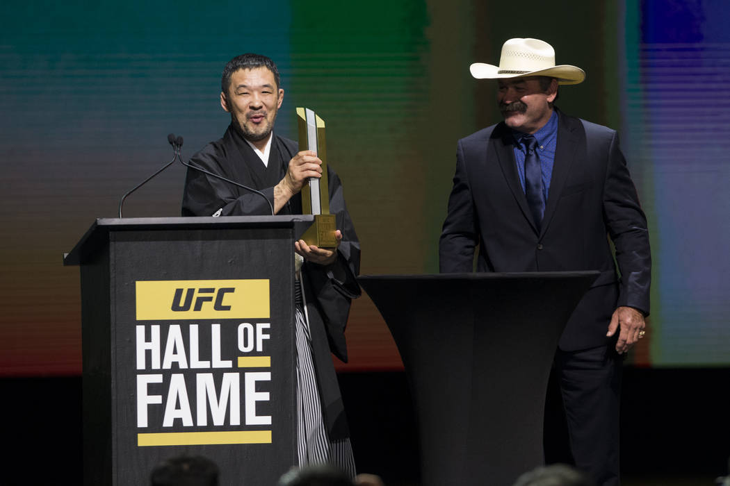 Kazushi Sakuraba, left, is inducted to the UFC Hall of Fame after a speech by fellow hall of famer Don Frye during an induction ceremony at the Park Theater inside the Monte Carlo hotel-casino in  ...