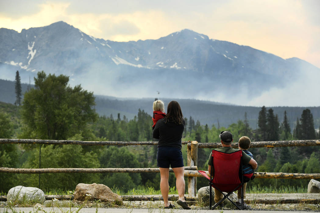 Amy Noraka, holding daughter Sage, 3, left, and her husband Chris Noraka, with son Tyler, 6, watch as helicopters dump water on a wildfire near the Peak 2 in Breckenridge, Colo., Thursday, July 6, ...