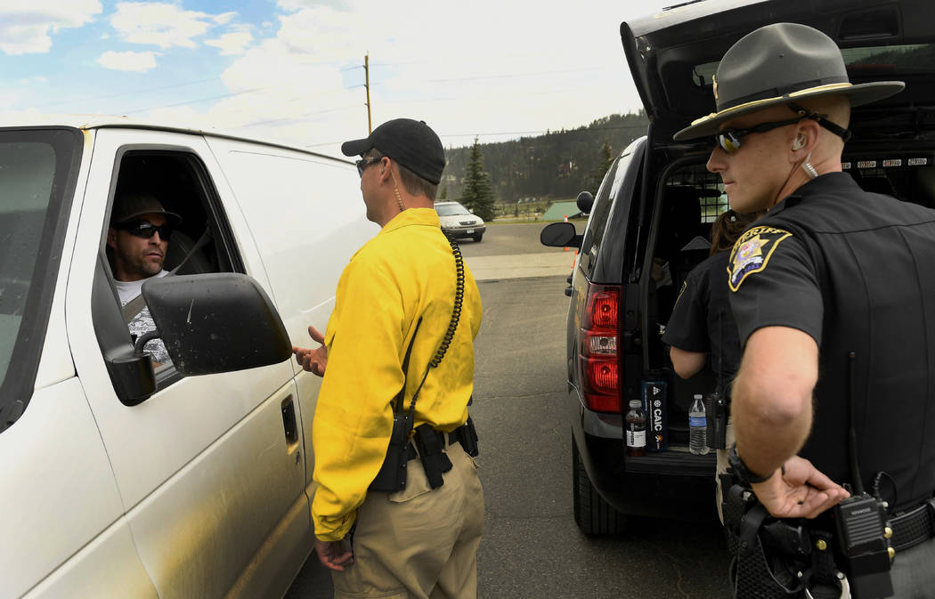 Summit County Sheriff's deputies SJ Hamit, middle, and Mike Schilling, talk to residents about access to the Peak 7 neighborhood in Breckenridge, Colo., Thursday, July 6, 2017. Firefighters were w ...