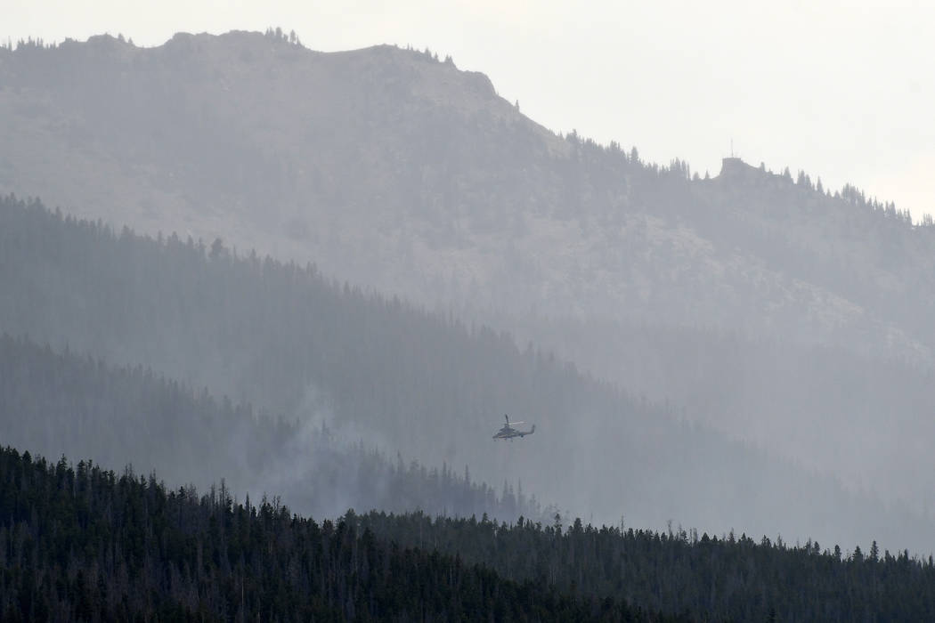 A helicopter makes water drops on a wildfire near the Peak 2 as it continues to burn in the White River National Forest between Breckenridge and Frisco, Colo., Thursday, July 6, 2017. Firefighters ...