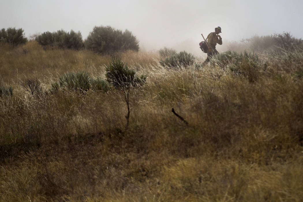 A firefighter walks along the fire line as flames burn grass and brush on Rattlesnake Ridge in Moxee, Wash., on Thursday, July 6, 2017. The fire burned more than 5,500 acres of mostly grass and br ...