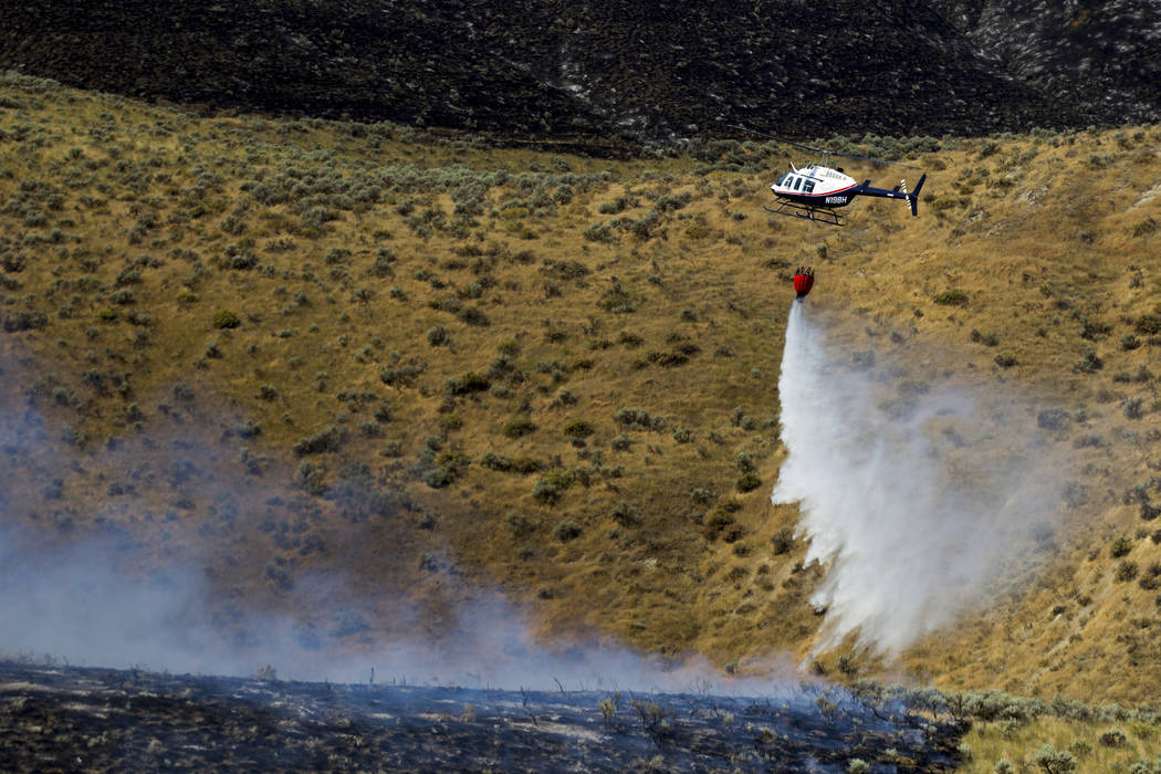 A helicopter dumps water on a brush fire on Rattlesnake Ridge in Moxee, Wash., on Thursday, July 6, 2017. The fire burned more than 5,500 acres of mostly grass and brush in less than 24 hours, and ...