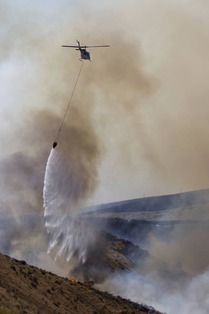 A helicopter dumps water along the fire line as the fire moves down Rattlesnake Ridge in Moxee, Wash., on Thursday, July 6, 2017. The fire burned more than 5,500 acres of mostly grass and brush in ...