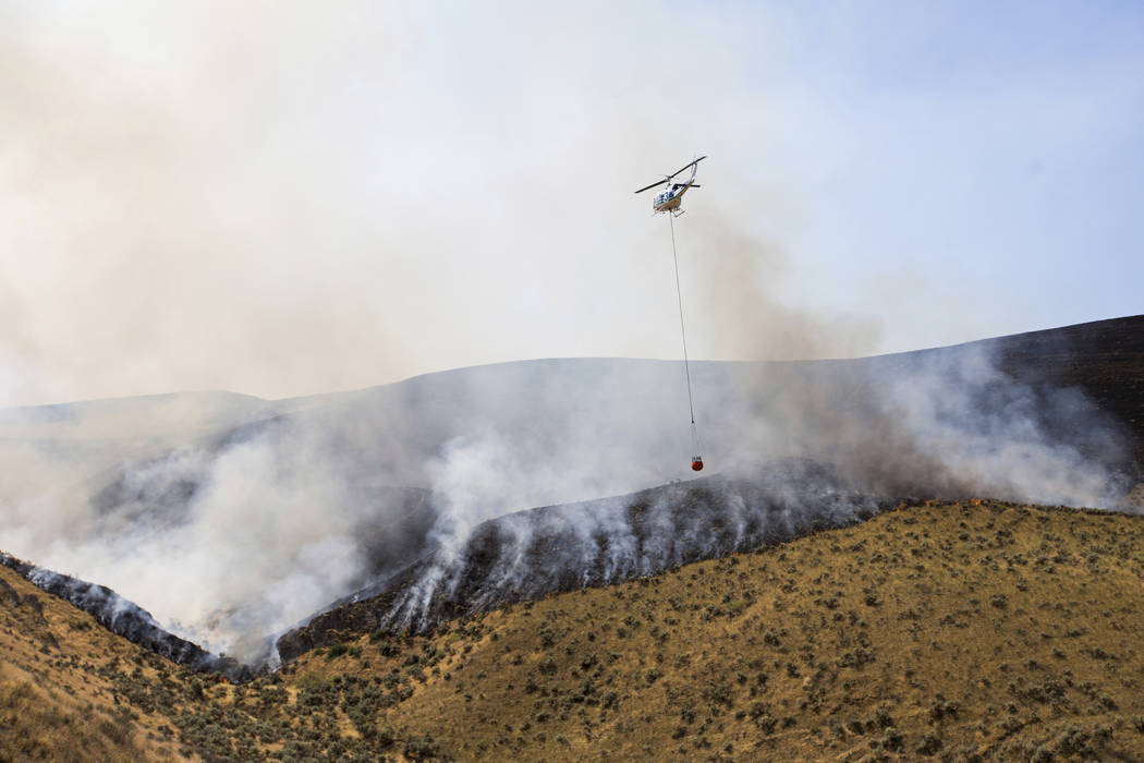A helicopter carries a bucket of water towards the fire line at Rattlesnake Ridge in Moxee, Wash., on Thursday, July 6, 2017. The fire burned more than 5,500 acres of mostly grass and brush in les ...