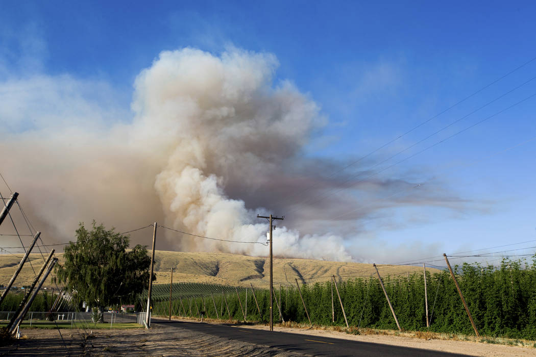 Smoke fills the sky as a brush fire burns on Rattlesnake Ridge in Moxee, Wash., on Thursday, July 6, 2017. The fire burned more than 5,500 acres of mostly grass and brush in less than 24 hours, an ...