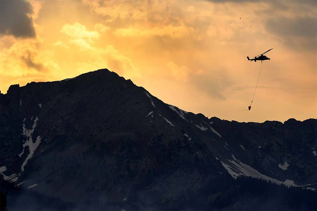 As the sun sets a helicopter makes water dumps on a wildfire near the Peak 2 in Breckenridge, Colorado, Thursday, July 5, 2017. Firefighters were working Thursday to keep the wildfire that's force ...